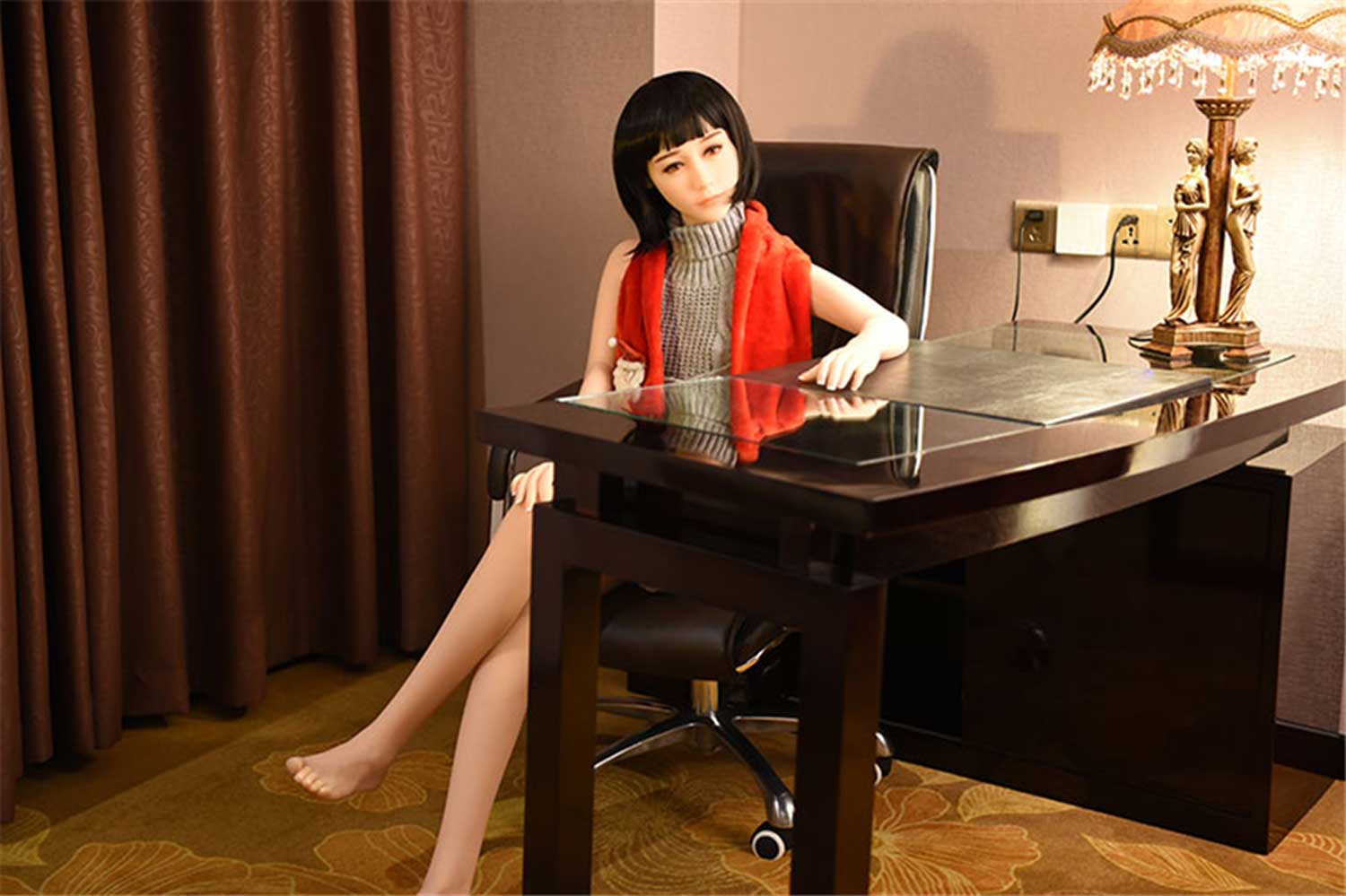 Sex doll sitting on a chair with hands on the table