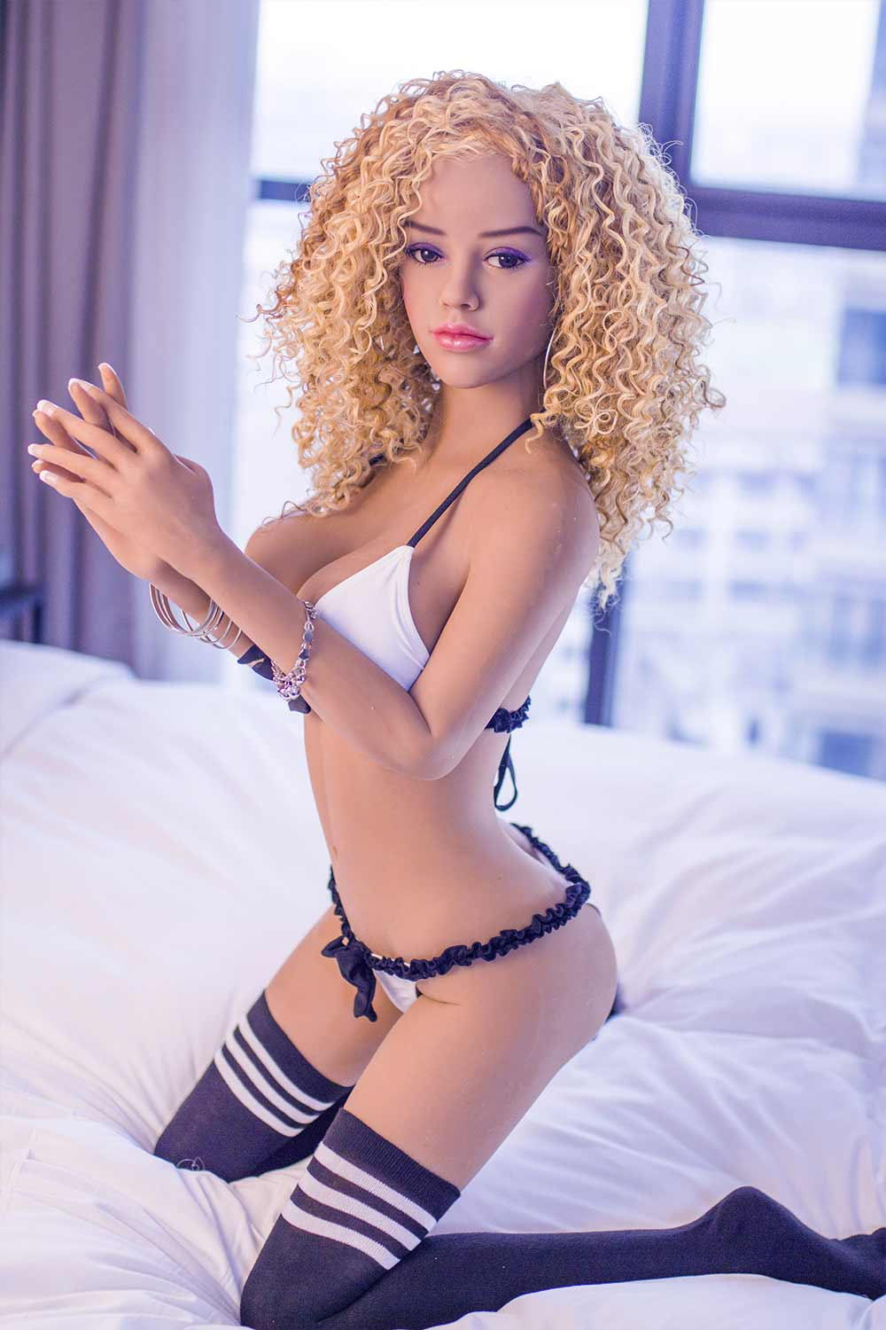Sex doll with legs kneeling on the bed