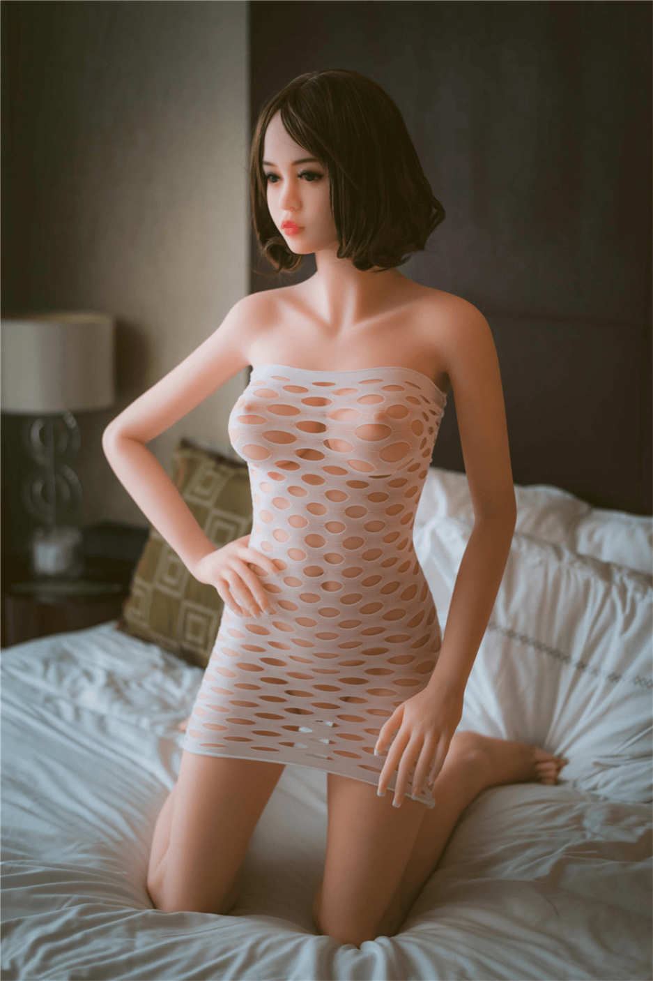sex doll kneeling on the bed
