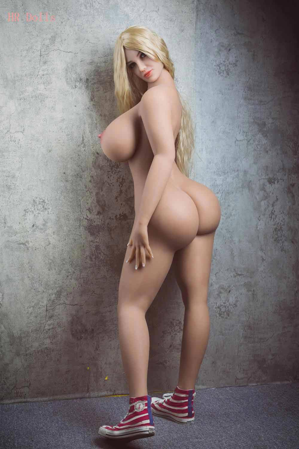 Big breasted sex doll standing facing the wall