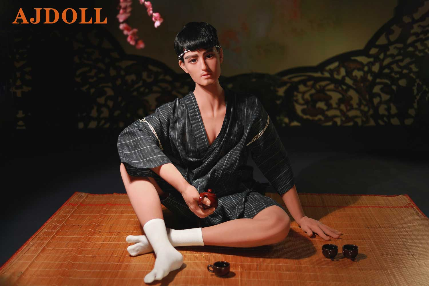 Male sex doll sitting on mat holding teapot