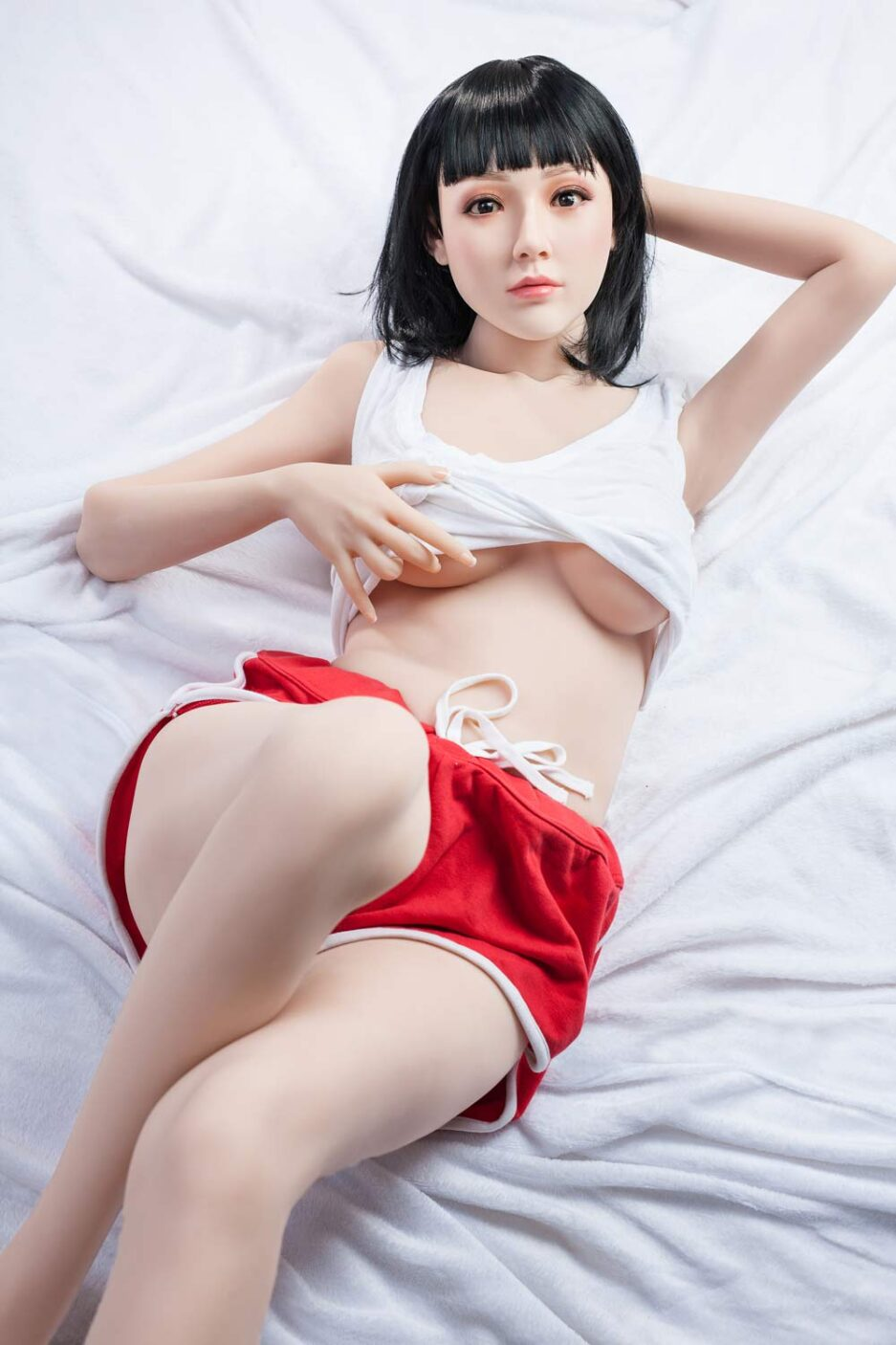 Silicone sex doll lying flat on bed and lifting clothes