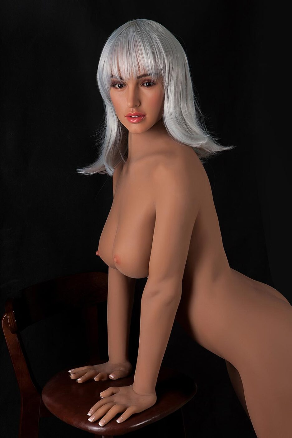 Silicone sex doll with both hands on a chair