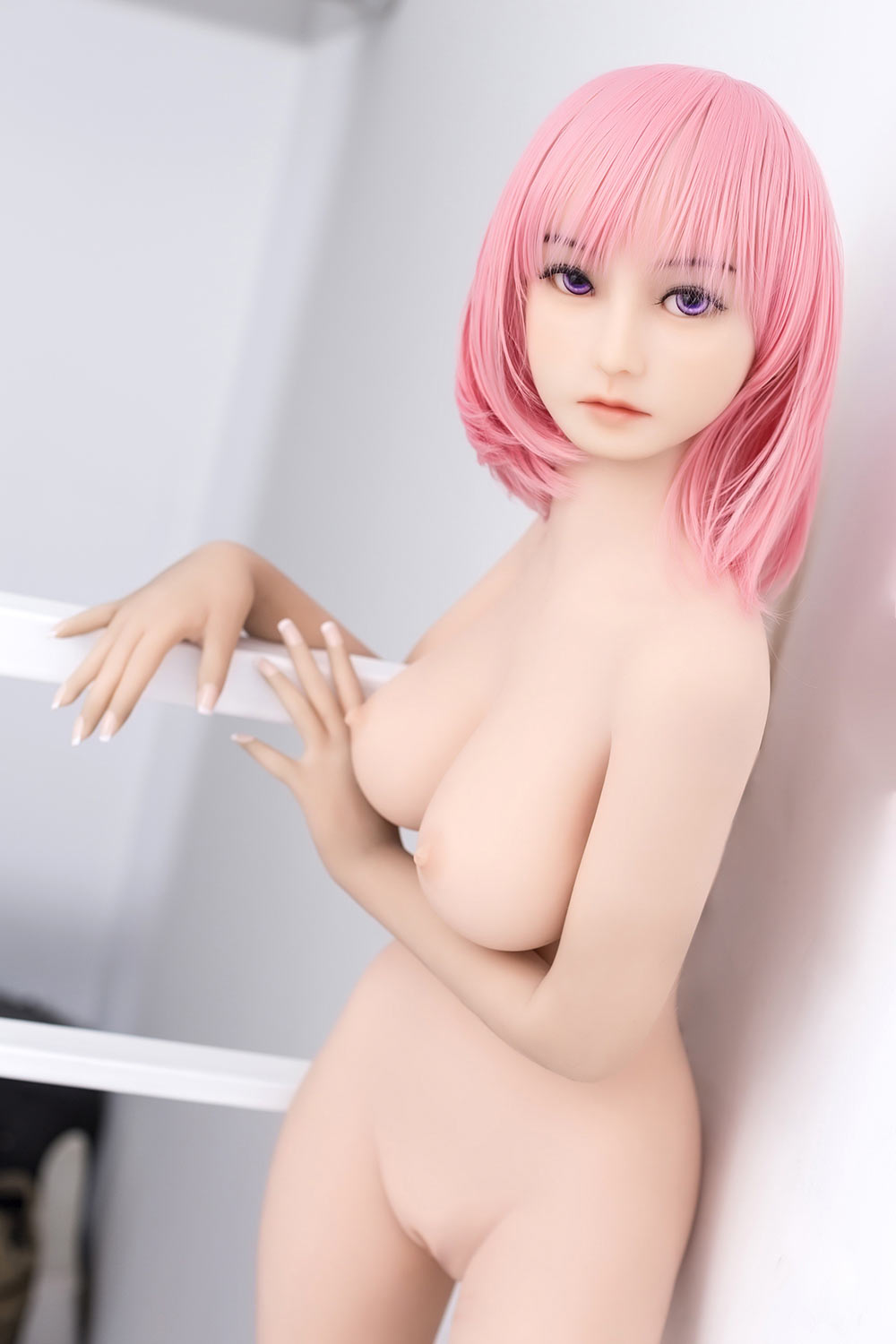 A mini sex doll with naked and flesh-colored breasts