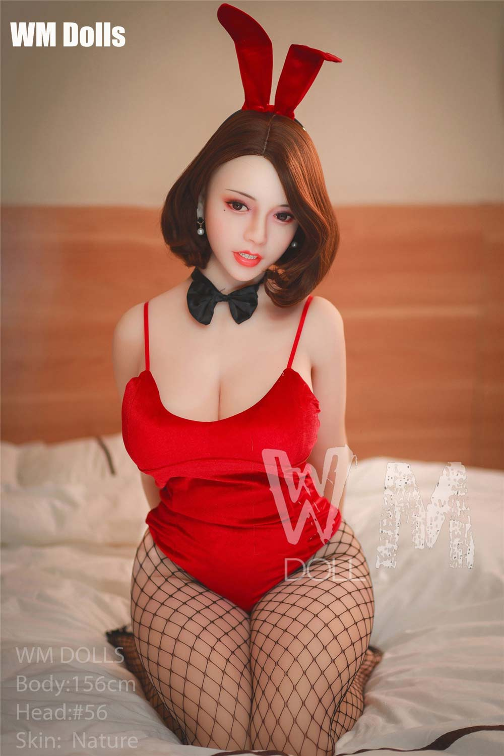 Big breasted sex doll kneeling on the bed