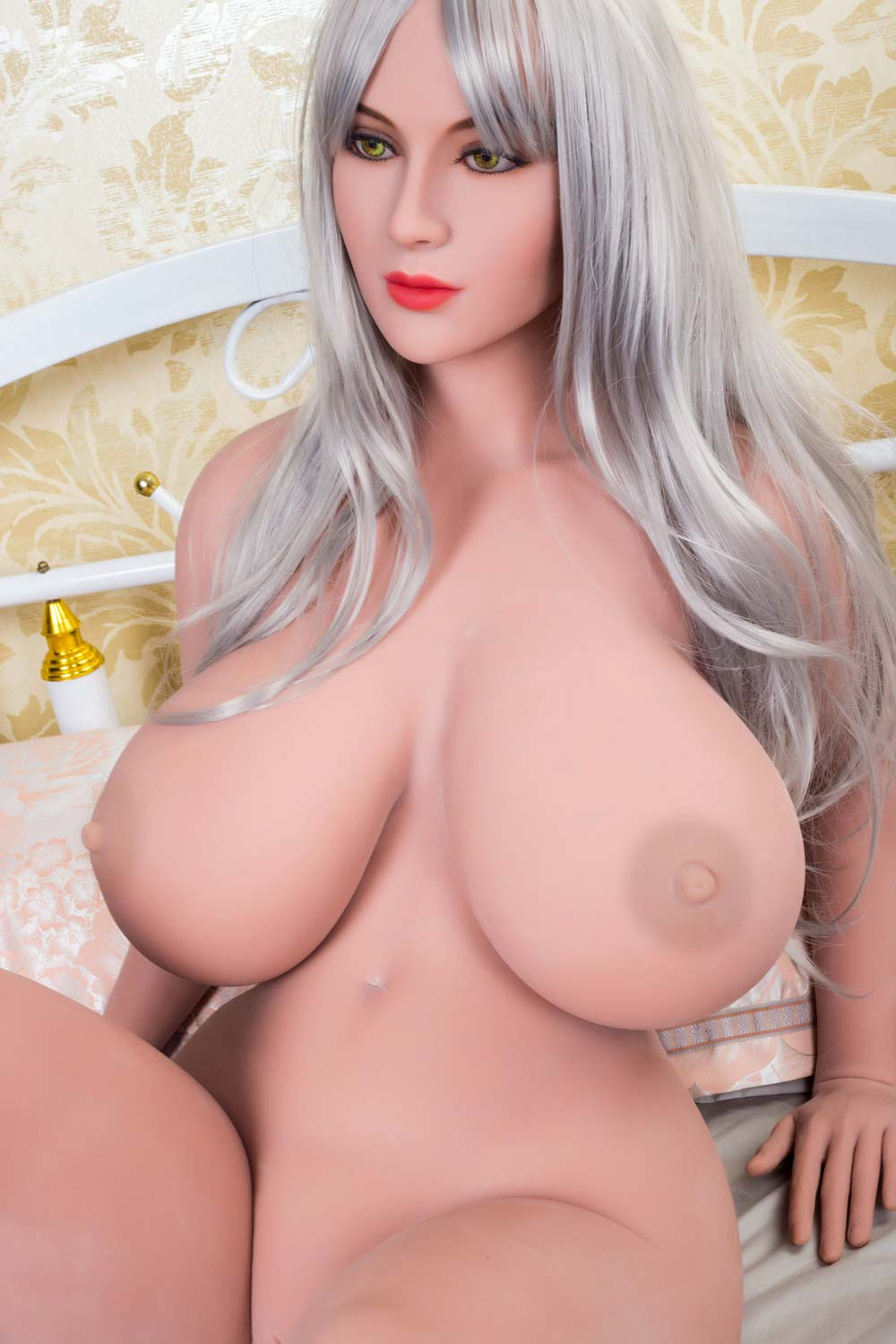 Big breasted sex doll sitting naked on the bed
