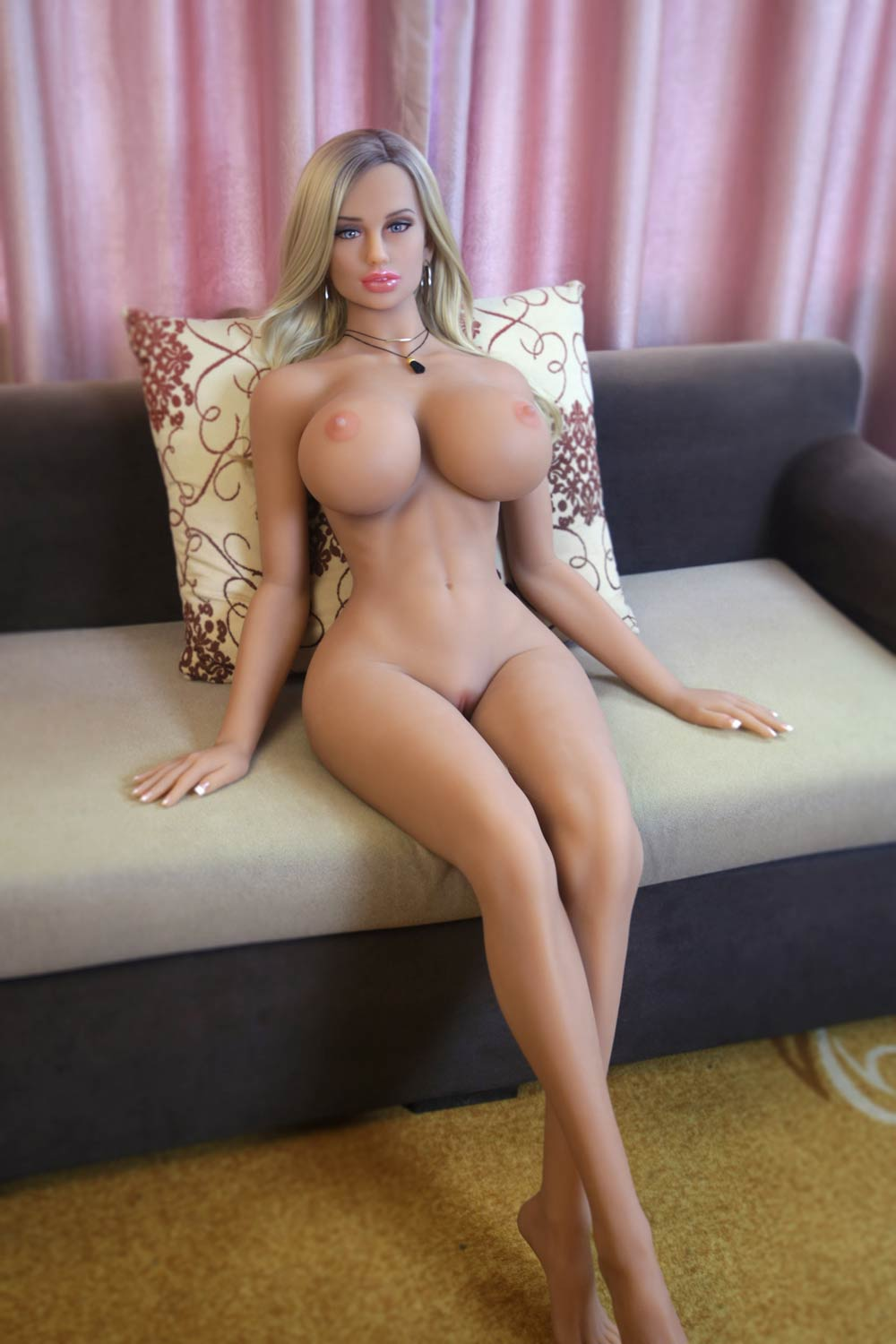 Big breasted sex doll sitting naked on the sofa