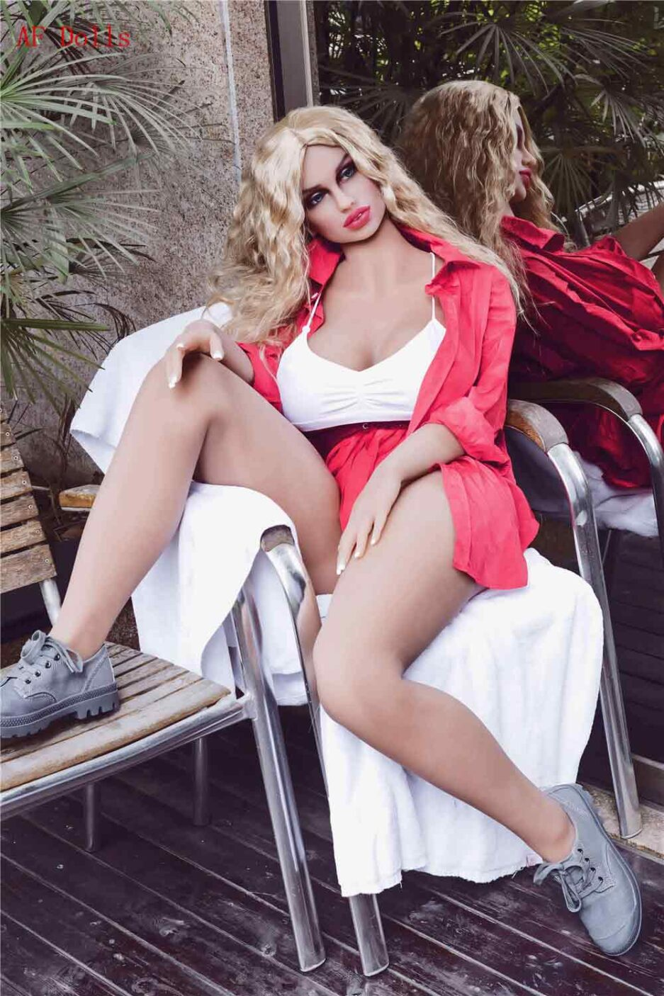 Big breasted sex doll sitting on a chair