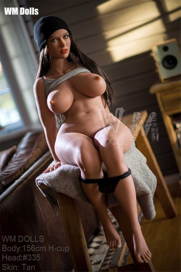 Big breasted sex doll sitting on the table