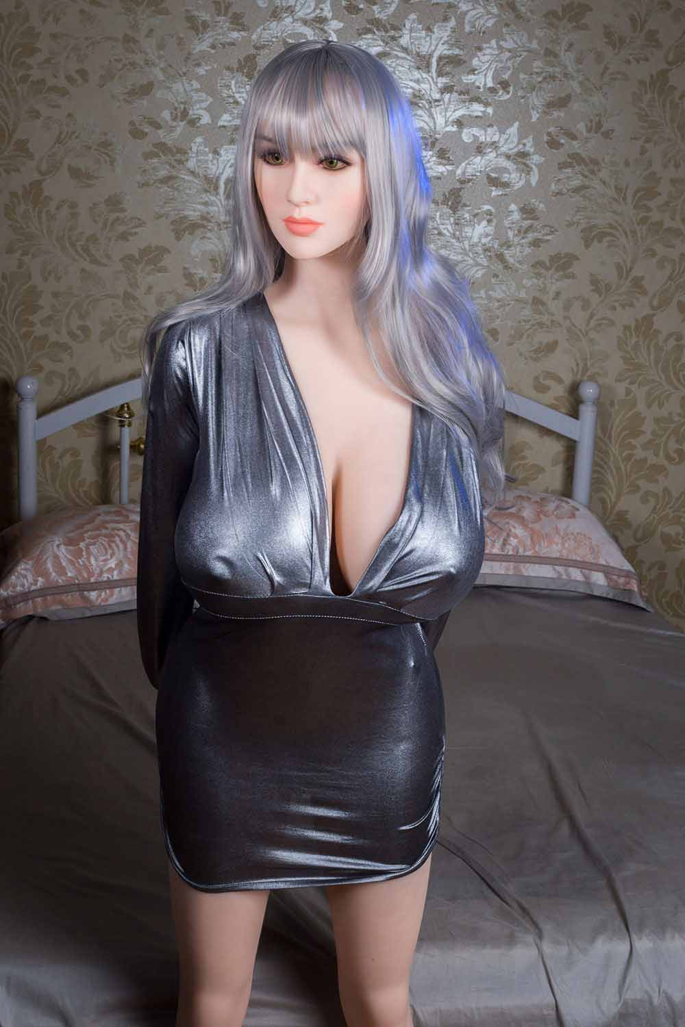 Big breasted sex doll standing by the bed