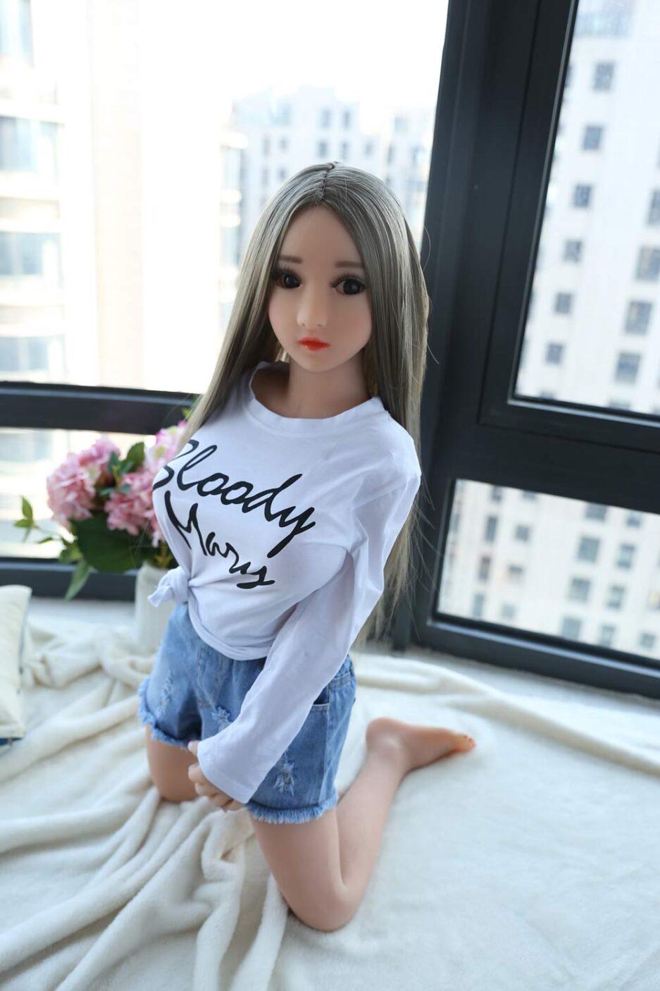Mini sex doll kneeling on the windowsill