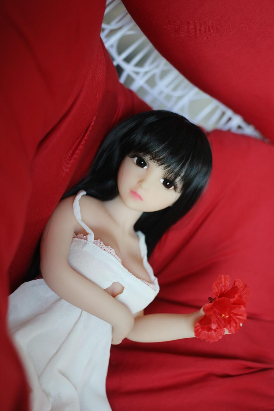 Mini sex doll with black long hair and red flower in hand