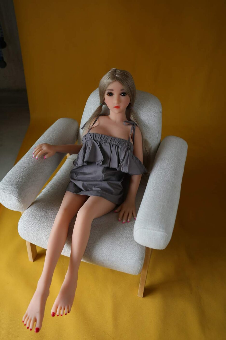 Mini sex doll with hand on chair
