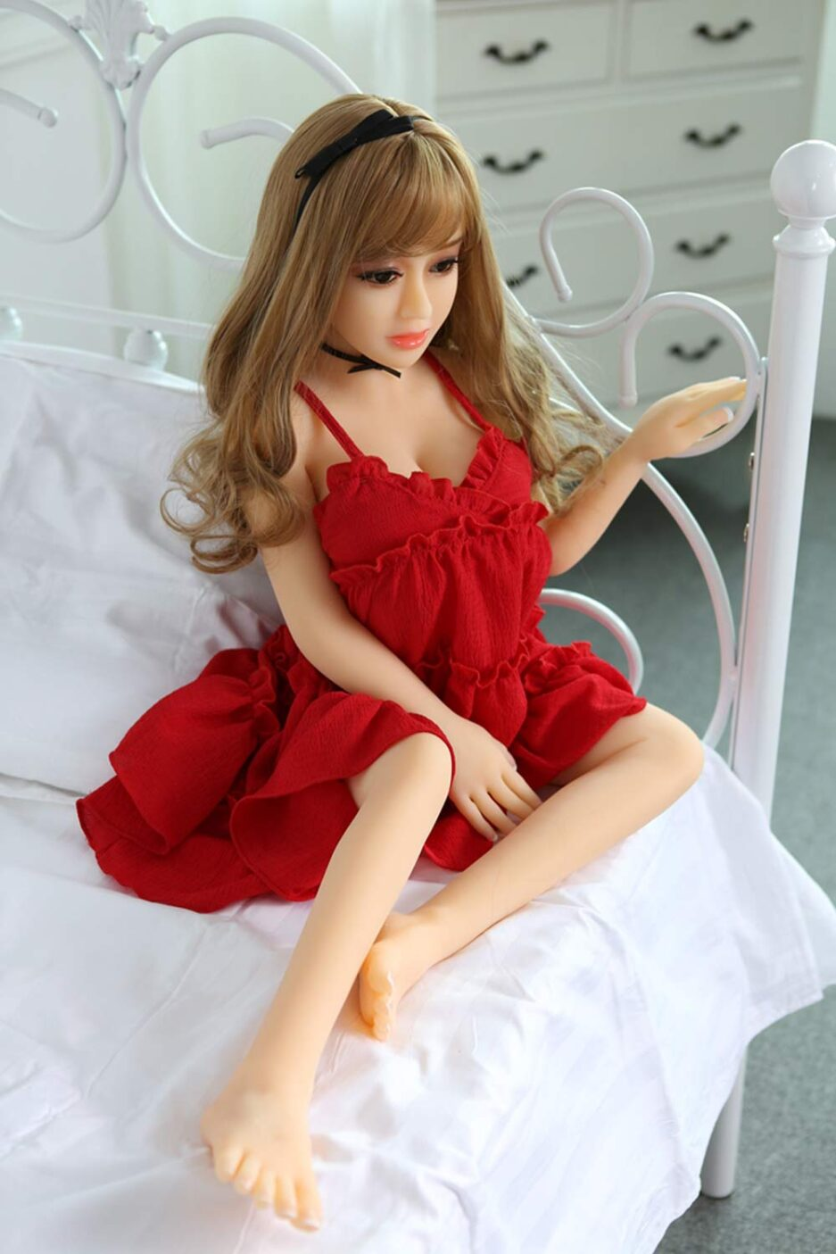 Mini sex doll with hands on the bed railing