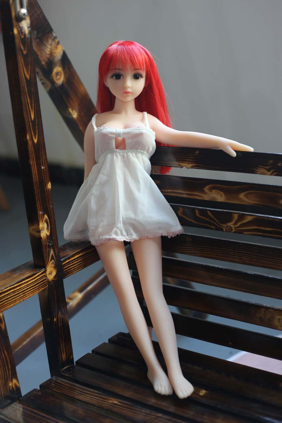 Mini sex doll with red long hair standing on a chair