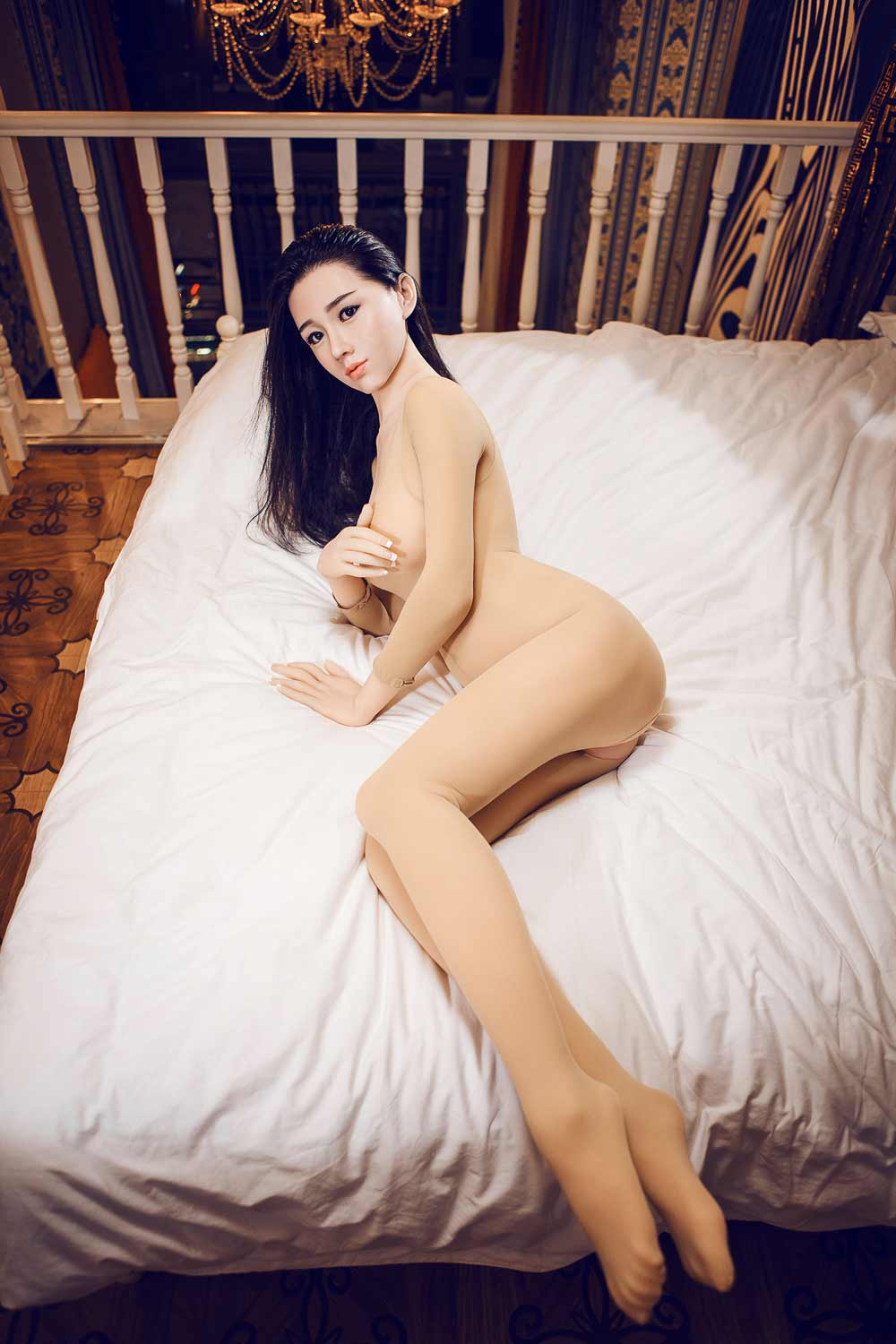 Silicone sex doll lying on the bed with hands covering breasts