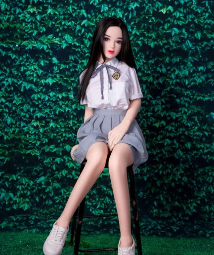 A mini sex doll sitting on a stool with hands between thighs