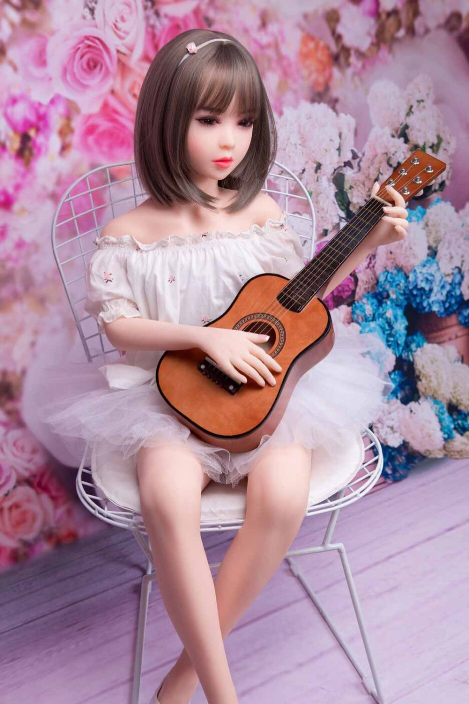 Mini sex doll sitting on a chair
