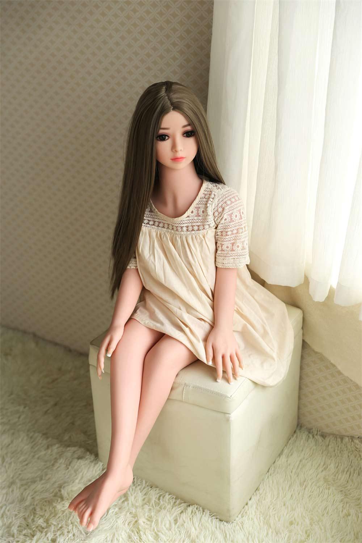 Mini sex doll sitting on a stool
