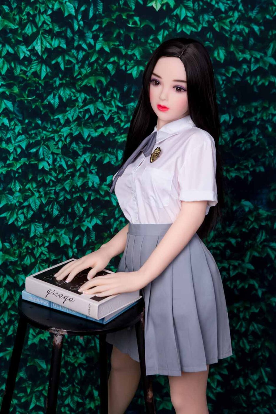 Mini sex doll with a book on a stool