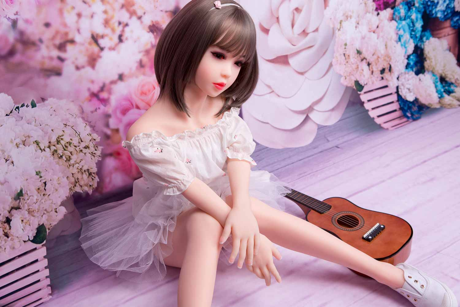Mini sex doll with guitar next to it
