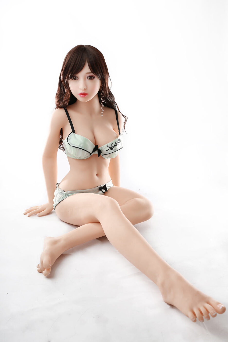 Mini sex doll with one foot on top of the other