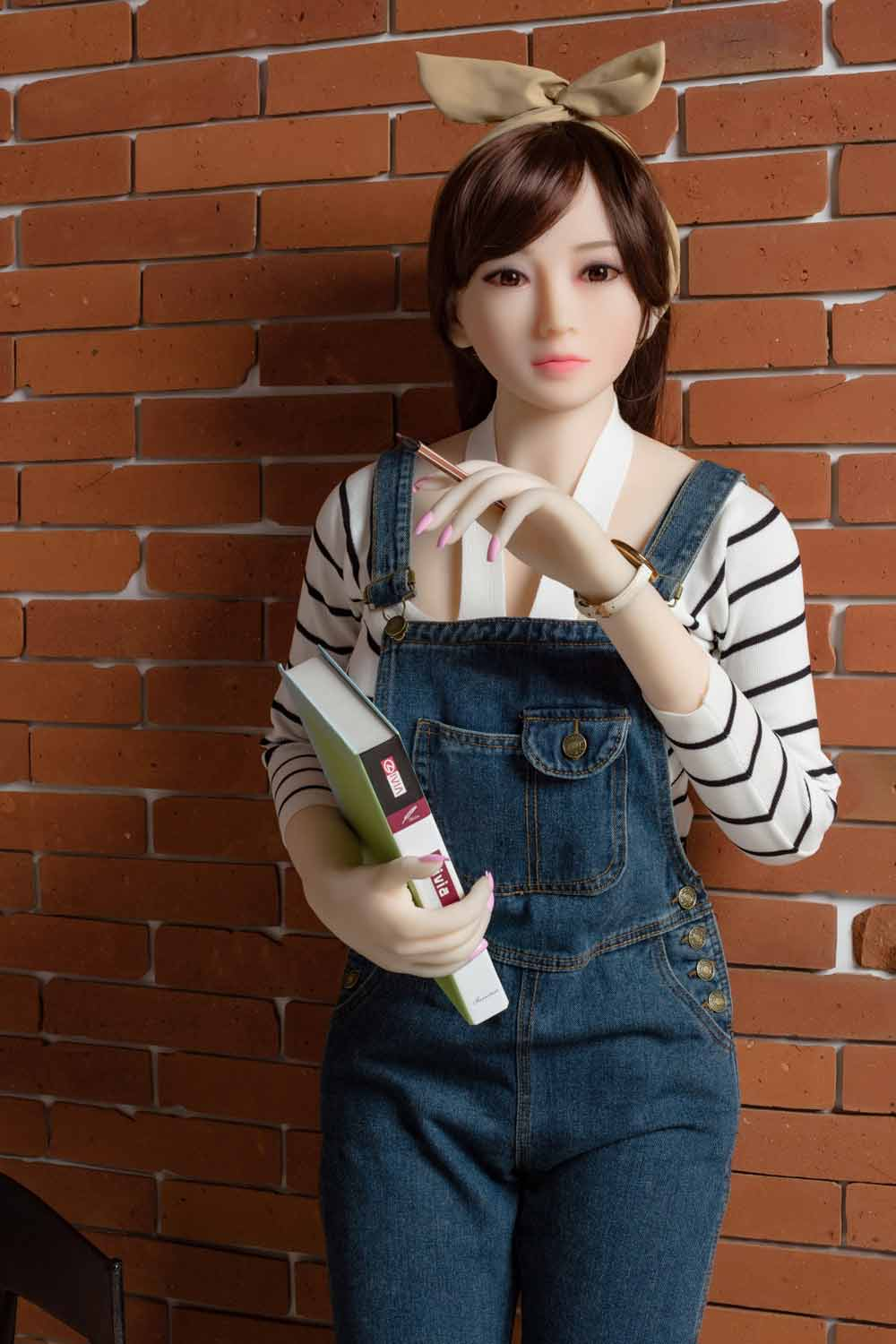 Sex doll with a book in one hand and a pen in one hand